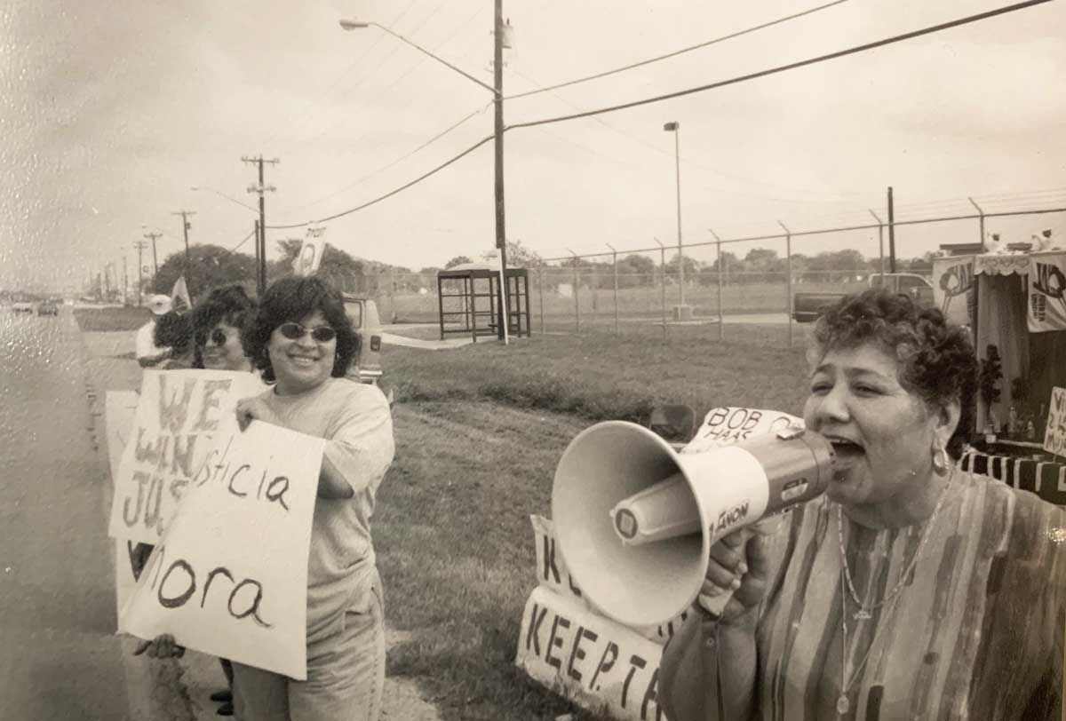 A black and white photo shows a female protester speaking into a bullhorn along a road with protest signs and other protesters beside her.