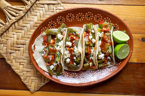 A plate of three tacos with green nopalitos is displayed on a traditional clay Mexican plate.