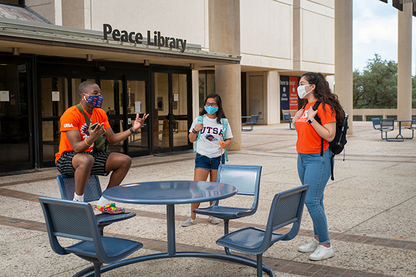 Three UTSA students wearing masks visit with each other outside the second-floor entrance to the John Peace Library.