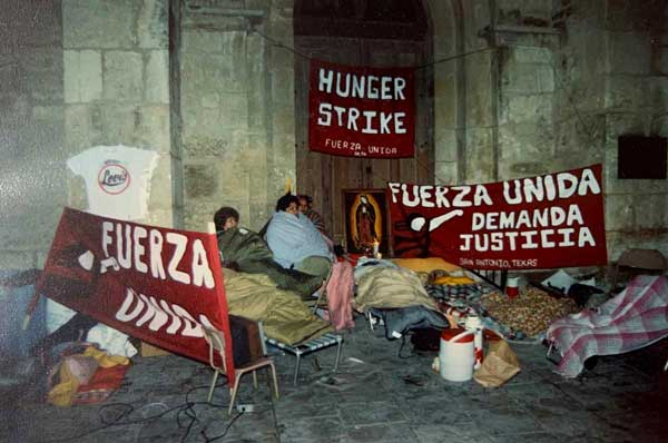 A photo from the 1990s shows protesters gathered in front of a building with signs declaring they are part of a hunger strike.