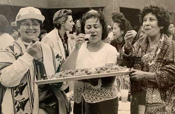 A black-and-white photo shows three women eating food from a platter and smiling.