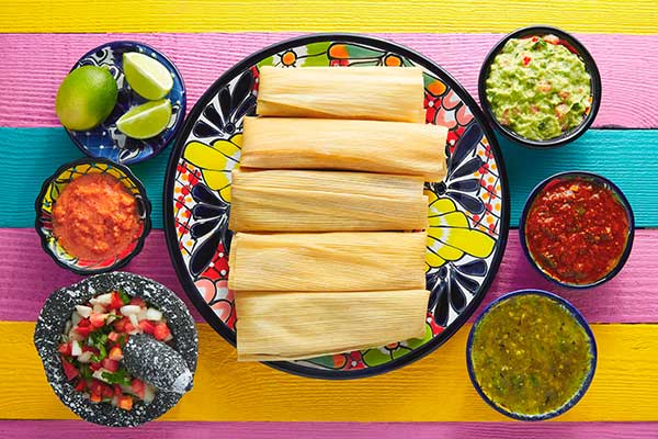 Five tamales are shown on a traditional colorful Mexican plate garnished with bowls of Mexican salsa on the side.