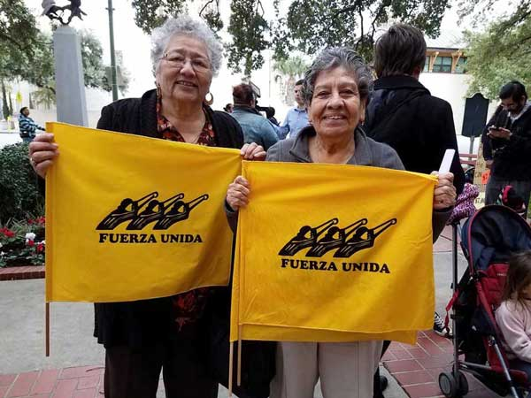"Photo of two smiling women holding flags displaying the words ""Fuerza Unida."""