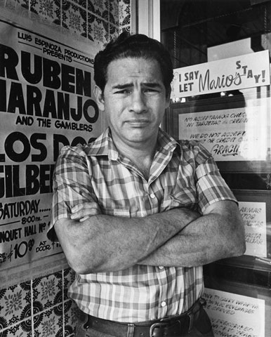 A black and white image of Mario Cantu standing outside of his restaurant in 1985.